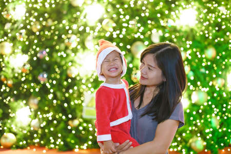 Asian mother holding her 1 year 11 months old baby in santa suit with christmas tree light as background