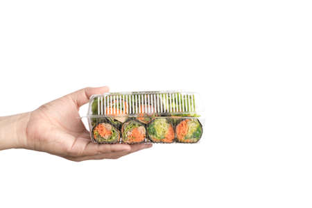Hand holding food plastic box of hydroponics vegetable salad roll wrapped by seaweed on white background Imagens