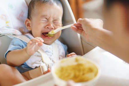 6 months old Asian baby refuse to eat food and crying over feeding time, Stock Photo