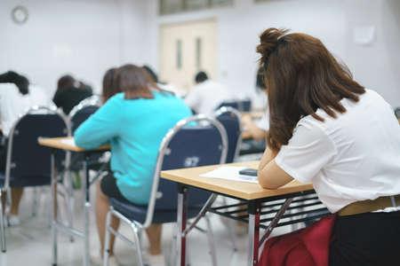 Asiatische Studenten, die eine Prüfung im Klassenzimmer ablegen