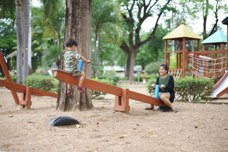 Asian boy about 2 year and 3 months in military suit playing seesaw and having fun with his mother at kid training playground for muscle development