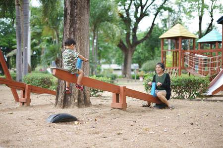 Aziatische jongen ongeveer 2 jaar en 3 maanden in militair pak wip spelen en plezier maken met zijn moeder op kinderspeeltuin voor spierontwikkeling