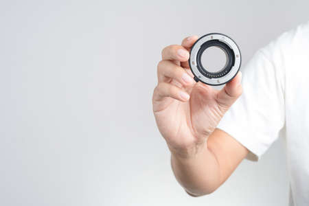 Hand holding macro extension tube, lens adapter ring with automatic focus function on white background 版權商用圖片 - 105004686