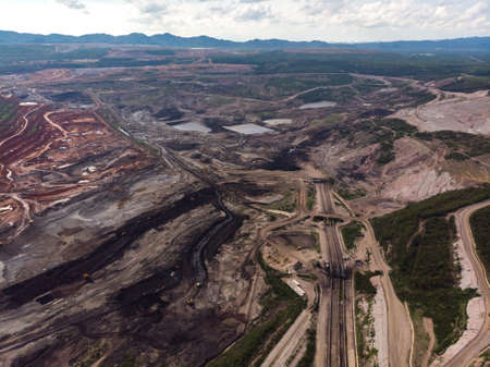 Open coal pit mine with heavy machine and ore transporting line in Asian country