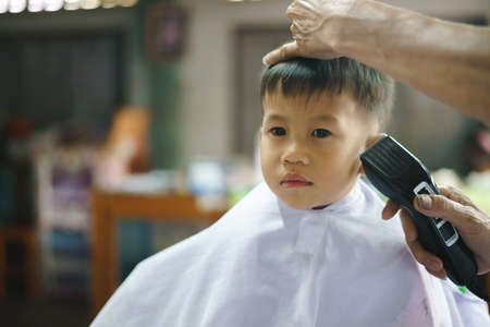 Asian boy about 2 years old getting haircut by professional barber at local shop 版權商用圖片