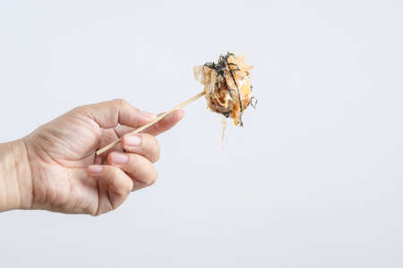 Hand holding Takoyaki, a flour ball  filled with octopus, Japanese street food on white background