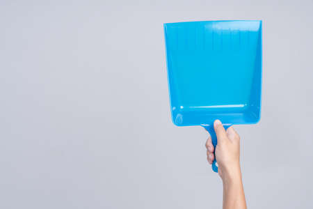 Hand holding portable blue plastic dustpan on white background