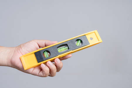 Hand holding spirit level tool for building or construction on white background 版權商用圖片
