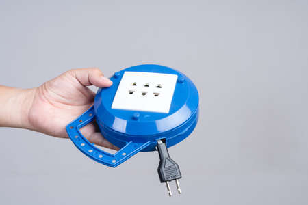 Hand holding portable round electric socket hub on white background