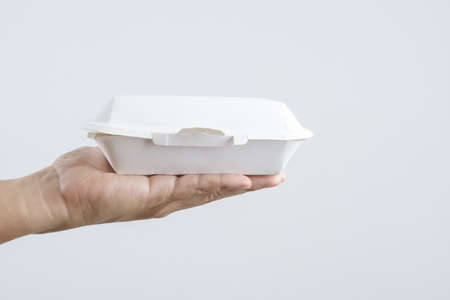 Hand holding Thai food in plant fiber paper food box on white background 版權商用圖片