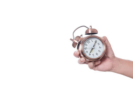 Hand holding vintage alarm clock setting at 7am and showing time over eight oclock for being late on white background