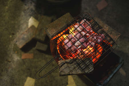 Pork barbecue over burned red hot charcoal on traditional Asian stove