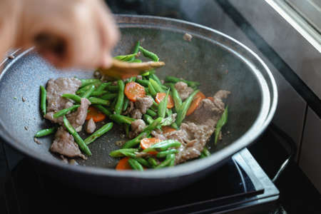Cooking stir fried string bean vegetables with pork and carrots