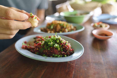 Eating raw spicy minced meat salad, a popular traditional Thai food for local people