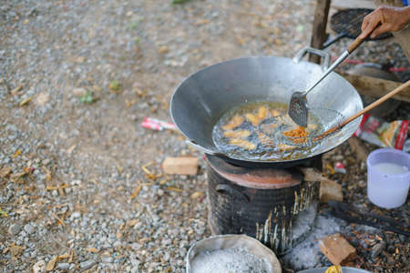 Thai fried banana snack cooking on an oil pan over Asian traditional charcoal stove 版權商用圖片