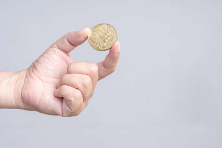 Hand holding golden bitcoin on white background