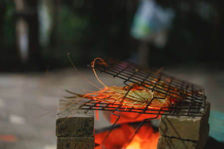 Grilled shrimp, prawn barbecue over Asian red hot charcoal stove