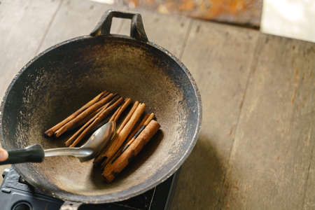 Frying cinnamon stick with pan over portable stove for enchant smell fragment 版權商用圖片