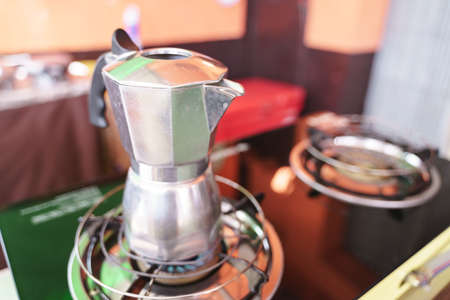 Steel espresso maker or moka pot on gas stove
