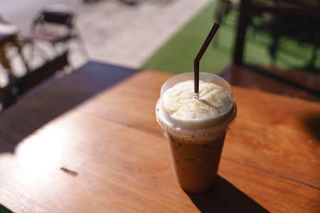 Plastic cup of iced latte coffee with milk froth and sweet syrup in cafe