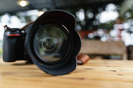 Modern camera lens for professional photography on wooden desk