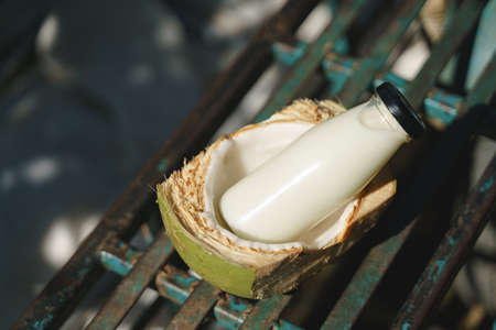 Glass bottle of coconut milk with half shell 版權商用圖片