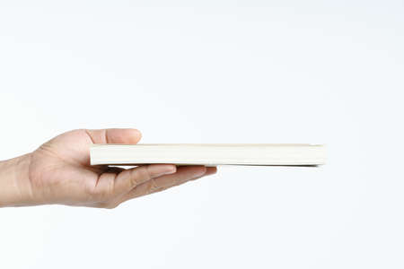 Hand holding book on white background 版權商用圖片