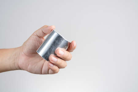 Hand holding adhesive aluminum foil tape for padding on white background