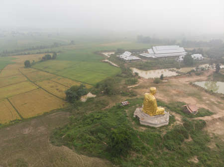 Morning cloud fog or mist over Thai public temple with big monk statue in rural village at Asian countryside