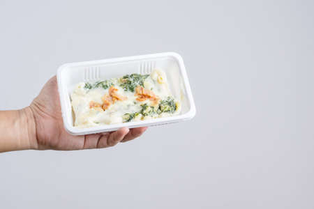 Hand holding spinach with cheese in plastic fast food box on white background