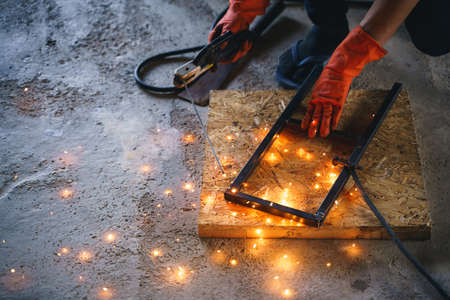 Worker labor welding wire metal for building and reinforcement DIY stand project