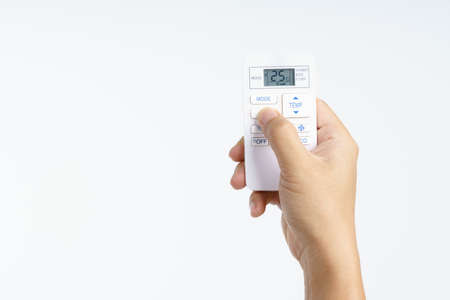 Hand holding air conditioner remote set temperature at 25 celsius on white background