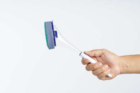 Hand holding new sponge brush with plastic handle on white background