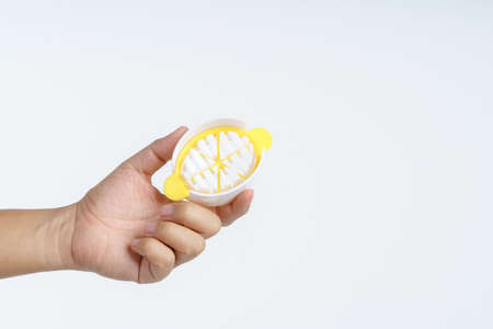 Hand holding plastic boiled egg slicer on white background