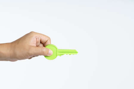 Hand holding big plastic key on white background