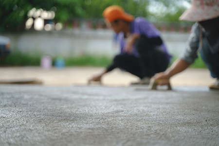 Asian worker labor working and scrubbing with concrete cement floor at house construction site
