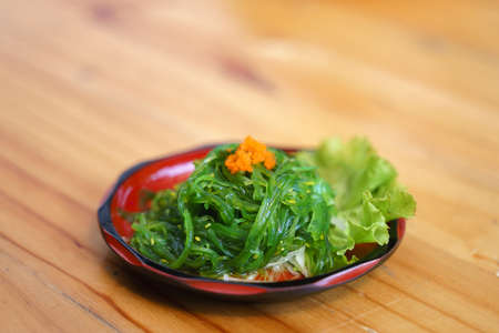 Seaweed salad with shrimp eggs, a Japanese food on weeden desk