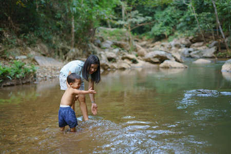 Asian mother in blue shirt with DIY chest pocket playing water with her son about 1 year and 9 months at  waterfall in Asian  countryside