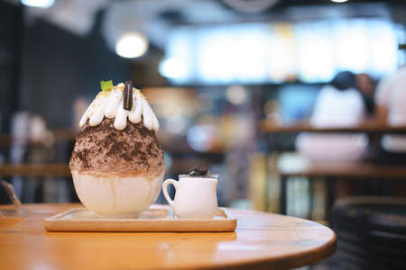 Bingsu or Asian Ice flake dessert with chocolate and sweet milk whip cream on top