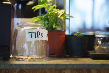 Glass tips jar in cafe with few Thai coins