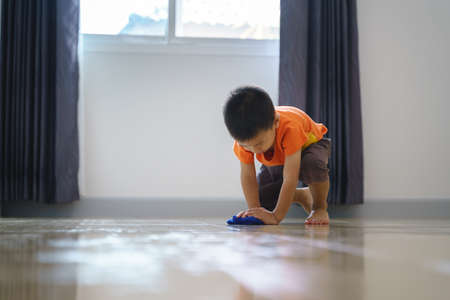 Asian boy about 3 year and 8 months doing chore by mop the house floor with cloth