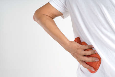 Hand holding hot water bag for pain relief at back or spine on white background Stockfoto