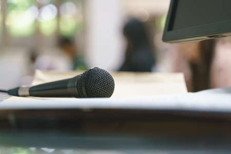 Handheld microphone at lecture room with asian students taking an exam