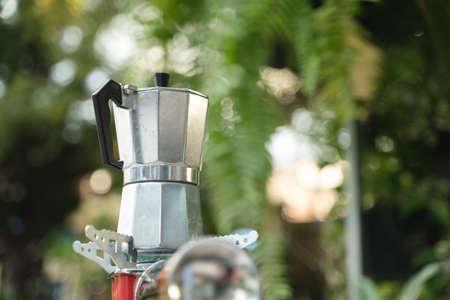 Steel espresso coffee maker or moka pot brewing on gas stove in green garden