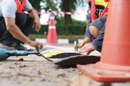 Security team installing safety road speed breaker or hump by using drill and hammer 版權商用圖片