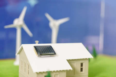 Solar cell panel on the roof tile of toy house with wind turbine generator in the background as alternative energy concept