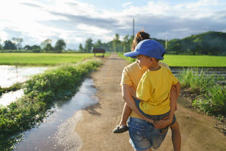 Asian Mother giving her son piggyback at rice field