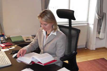 Happy business woman doing reearch at her desk