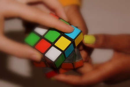 Rubik cube held in the hands of 3 multi-national youngsters