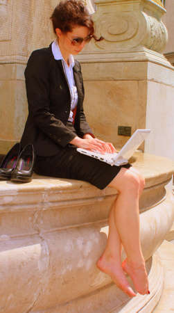 bare feet: Business Woman working outside on her laptop Stock Photo
